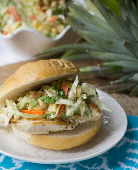 Chicken Sandwich with Pineapple Slaw on a plate with bowl of slaw in background.
