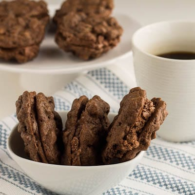 Three cookies arranged in a bowl with cup of coffee.