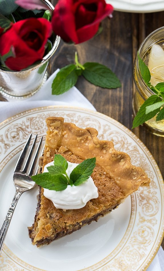Kentucky Derby Pie has a gooey chocolate and walnut filling with a splash of bourbon. Top with bourbon whipped cream for a delicious southern dessert.