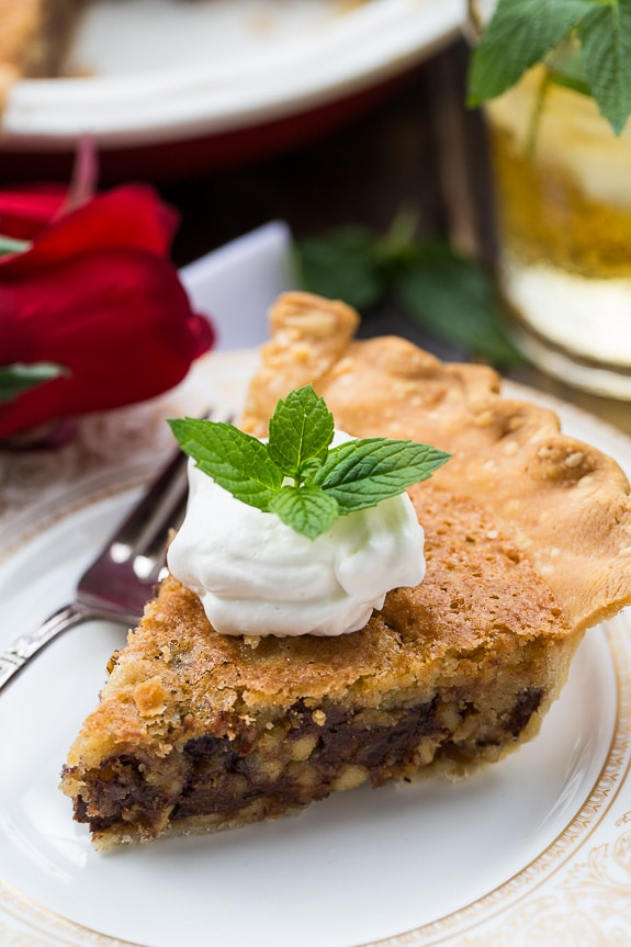 Kentucky Derby Pie with a gooey chocolate and walnut filling. Top with bourbon whipped cream for a delicious southern dessert.