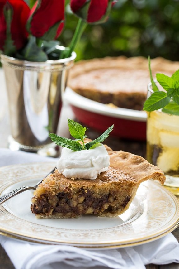 Kentucky Derby Pie has a gooey chocolate and walnut filling with a splash of bourbon. Topped with bourbon whipped cream for a fabulous southern dessert!