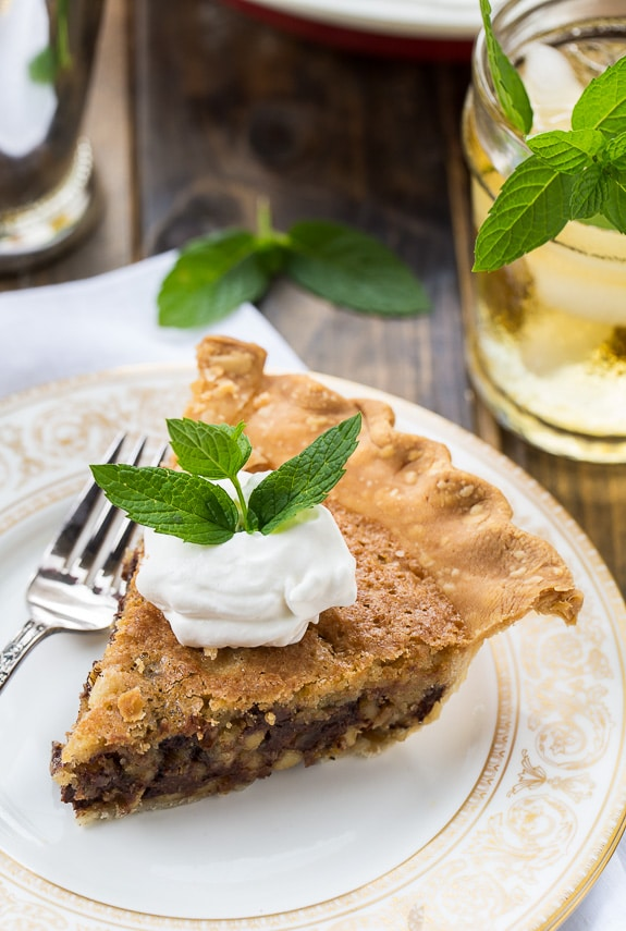 Kentucky Derby Pie has a gooey chocolate and walnut filling with a splash of bourbon. Topped with bourbon whipped cream for a truly delicious southern dessert.