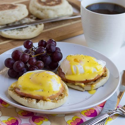 Eggs Benedict on a plate with red grapes with a cup of coffee.
