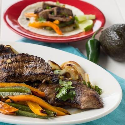 Grilled Skirt Steak Fajitas on a white serving platter.