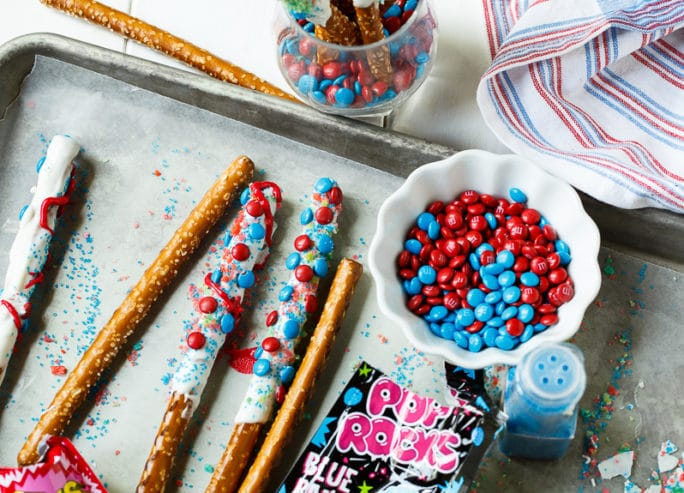 Firecracker Pretzel Rods for the 4th of July. Covered in Pop Rocks candy.