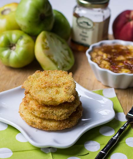 Fried Green Tomatoes on a small plate with green tomatoes and pepper jelly sauce in background.