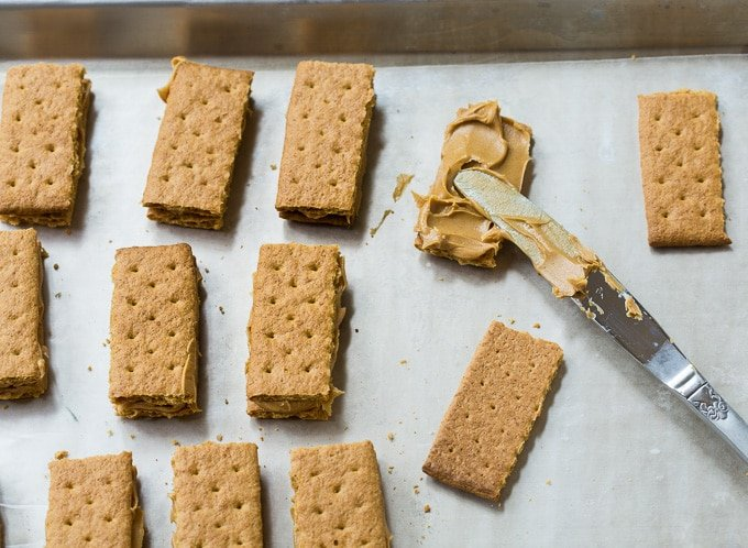 Spread peanut butter on graham crackers.