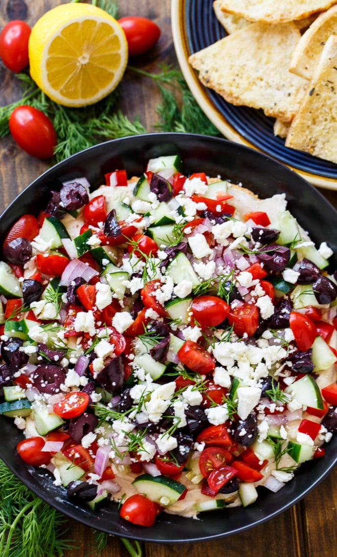 Creamy Greek Dip with cream cheese, hummus, tomatoes, cucumber, olives, feta, and fresh dill.
