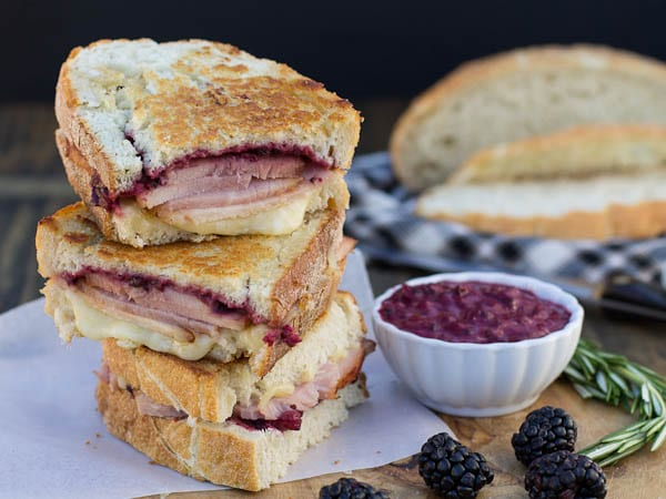 Ham Panini slices stacked up with bowl of blackberry mustard next to them.