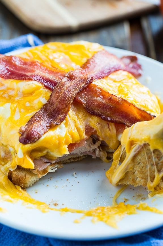 Kentucky Hot Brown with turkey, ham, and tomato, a cream gravy, a mound of gooey, melted cheddar cheese, and bacon. What a sandwich!