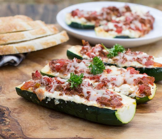 Three Zucchini Boats on a wooden cutting board.
