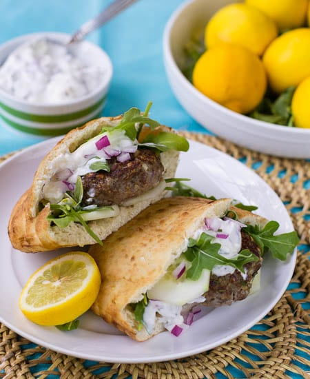Mediterranean Lamb Burger on a plate with tzatziki sauce and lemons in background.