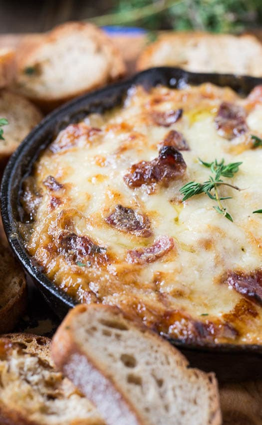 Hot Caramelized Onion Dip in a small cast iron skillet surrounded by toasted baguette slices.