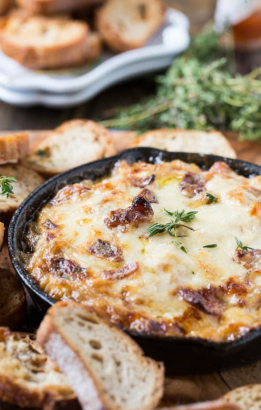 Onion Dip with Bacon and Gruyere surrounded by thyme and fresh baguette slices.