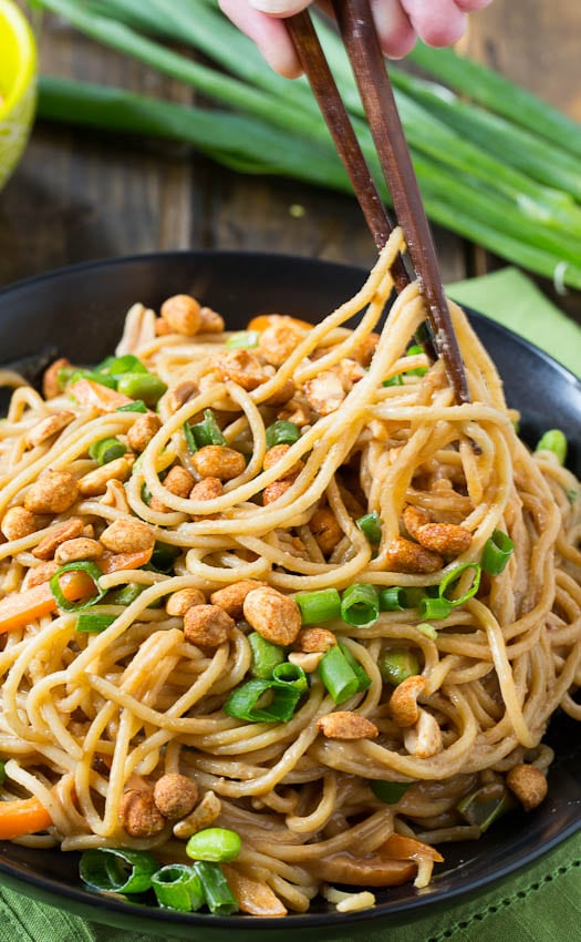 Peanut Sesame Noodles in a black bowl with green onions.