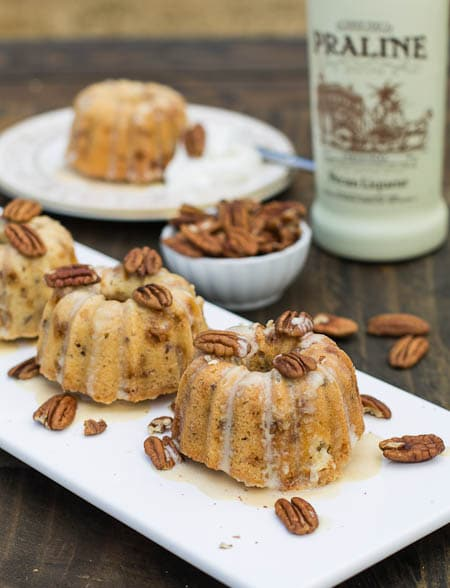 Mini Bundt Cakes on a serving platter surrounded by pecans.