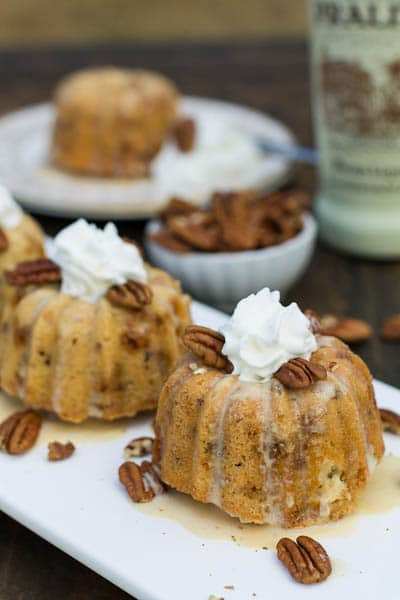Mini Toffee Budt Cakes topped with whipped cream and pecans.