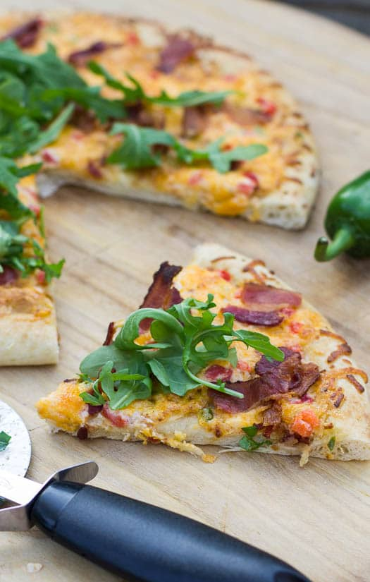 Pimiento Cheese Pizza topped with arugula on a wooden pizza peel.