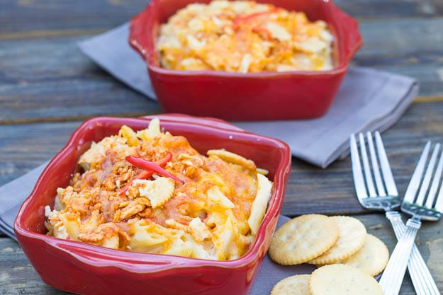 Mac and Pimiento Cheese in red baking dish with ritz crackers beside it.