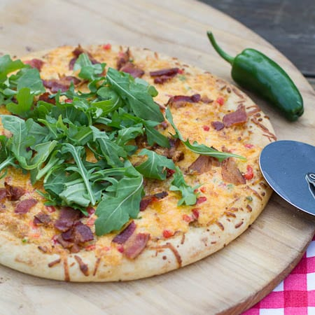 Whole Pimiento Cheese Pizza with bacon and arugula on a pizza peel.