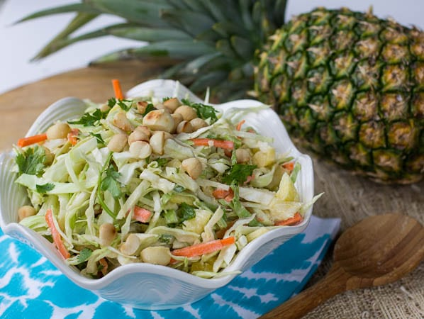 Pineapple Slaw in a white bowl with whole pineapple in background.