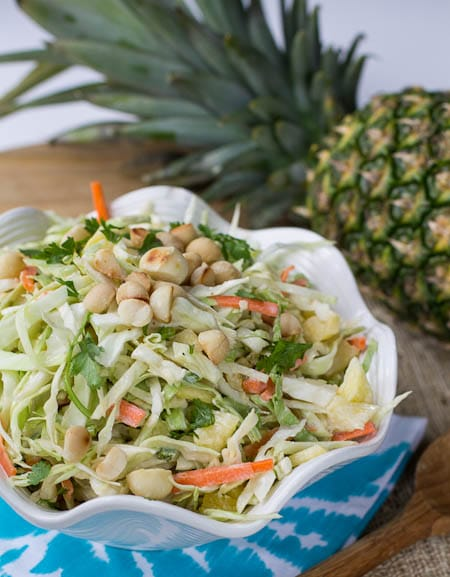 Pineapple Macadamia Slaw in white serving bowl with whole pienapple in background.