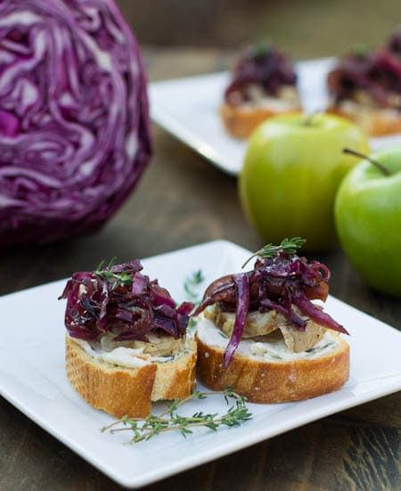 Crostini on a plate with red cabbage in background.
