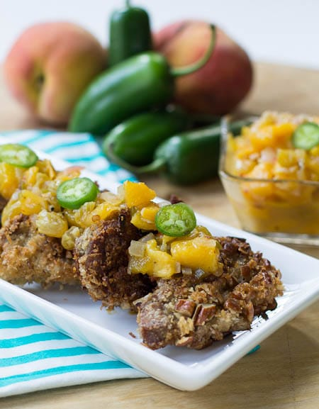 Pecan-Crusted Pork Medallions with peach chutney, and jalapenos in background.