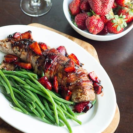 Pork Tenderloin with Balsamic Strawberries on a platter and a bowl of strawberries.