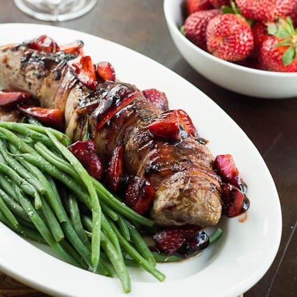 Pork Tenderloin with strawberries on a white serving platter with green beans.