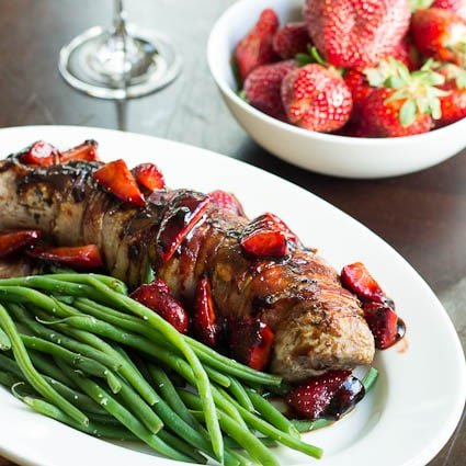 Pork Tenderloin with Strawberries on a white platter with green beans.