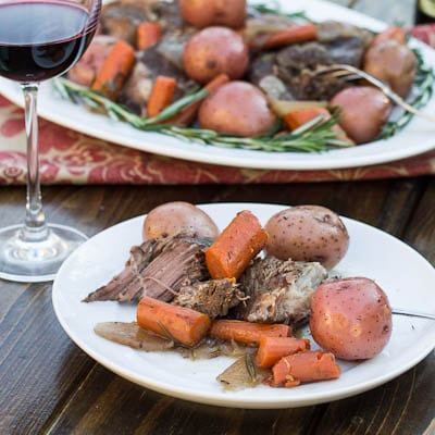 Single serving of Pot Roast on a white plate with a glass of red wine.