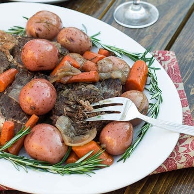 Pot Roast on a serving platter with fresh rosemary.
