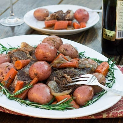 Pot Roast on a white serving platter surrounded with fresh rosemary.