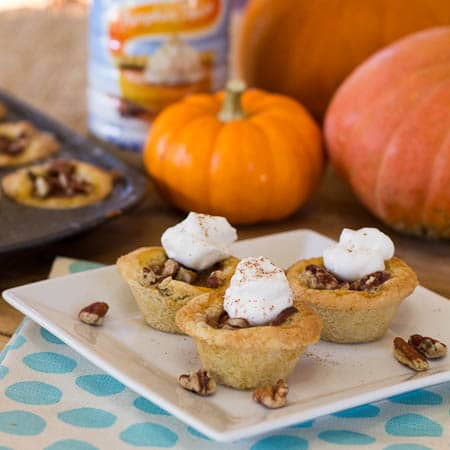 Pumpkin Tassies in Sugar Cookie Crust on a plate with pumpkins in background.