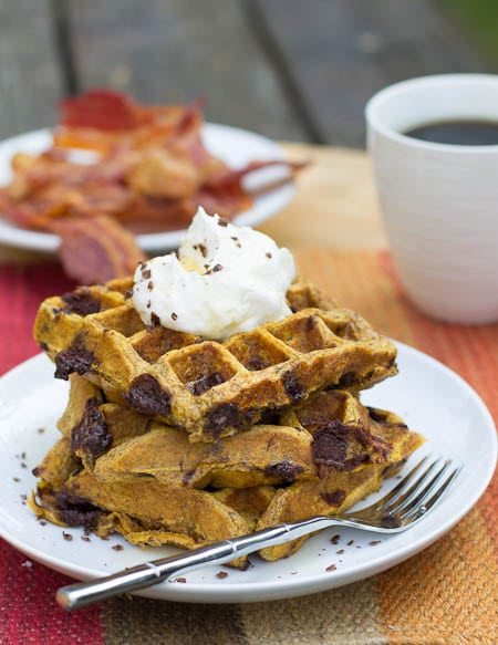Three Pumpkin Waffles stacked on a plate with bacon in background.