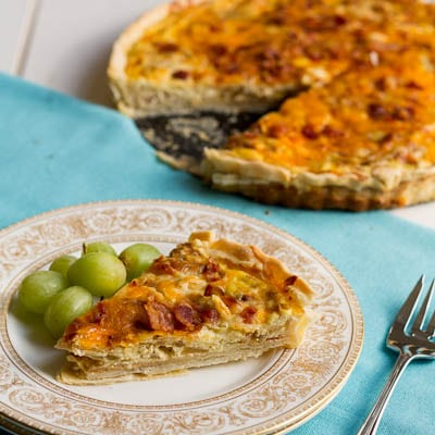 Slice of quiche on a plate with grapes.