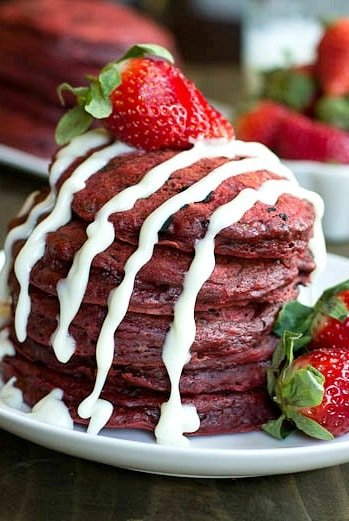 Stack of Red Velvet Pancakes with Cream Cheese Glaze on a white plate.