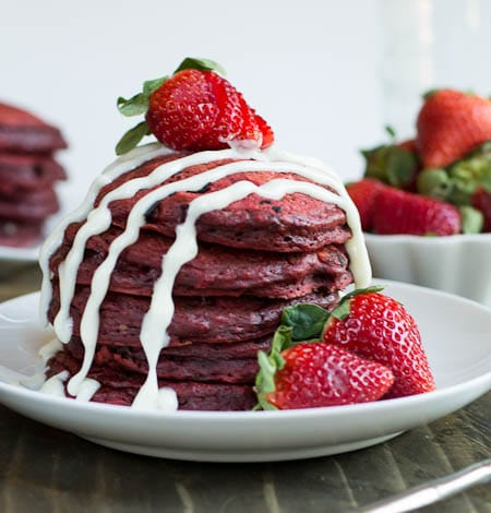 Close-up of stack of red velvet-flavored pancakes with cream cheese glaze and strawberries.
