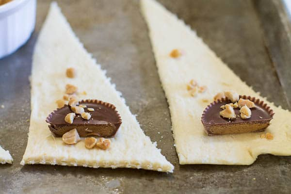 Triangles of crescent roll dough with Reese's cup and chopped peanuts on them.