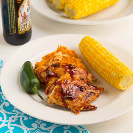 Root Beer Glazed Chicken on a plate with a jalapeno and corn on the cob.