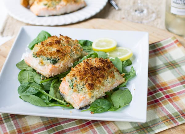 Two pieces of Baked Salmon with Mascarpone Spinach on plate with fresh spinach.