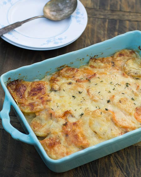 Caramelized Onion and Potato Gratin in blue baking dish with plates and spoon beside it.