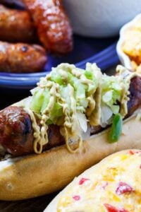 Grilled Brats topped with Pimento cheese and Green Tomato Chow Chow.