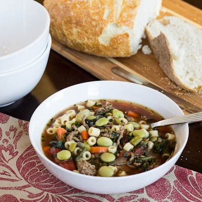 Bowl full of minestrone with bread in background.