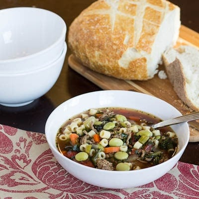 White bowl full of Southern Minestrone with bread.