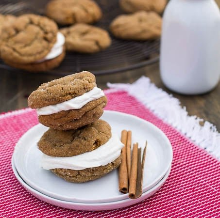 Two Gingerbread Sandwich Cookies on small plate with cinnamon sticks.