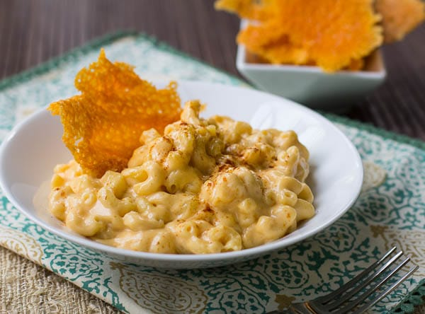 Bowl full of mac and cheese topped with a cheese crisp.