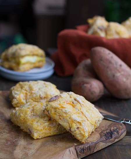 Three biscuits on a cutting board with sweet potatoes in background.