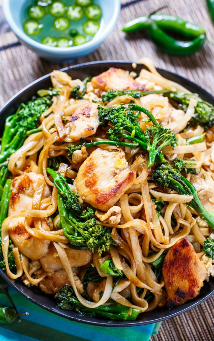 Thai Stir-Fried Noodles with Chicken and Broccolini in a black bowl with jalapenos in background.